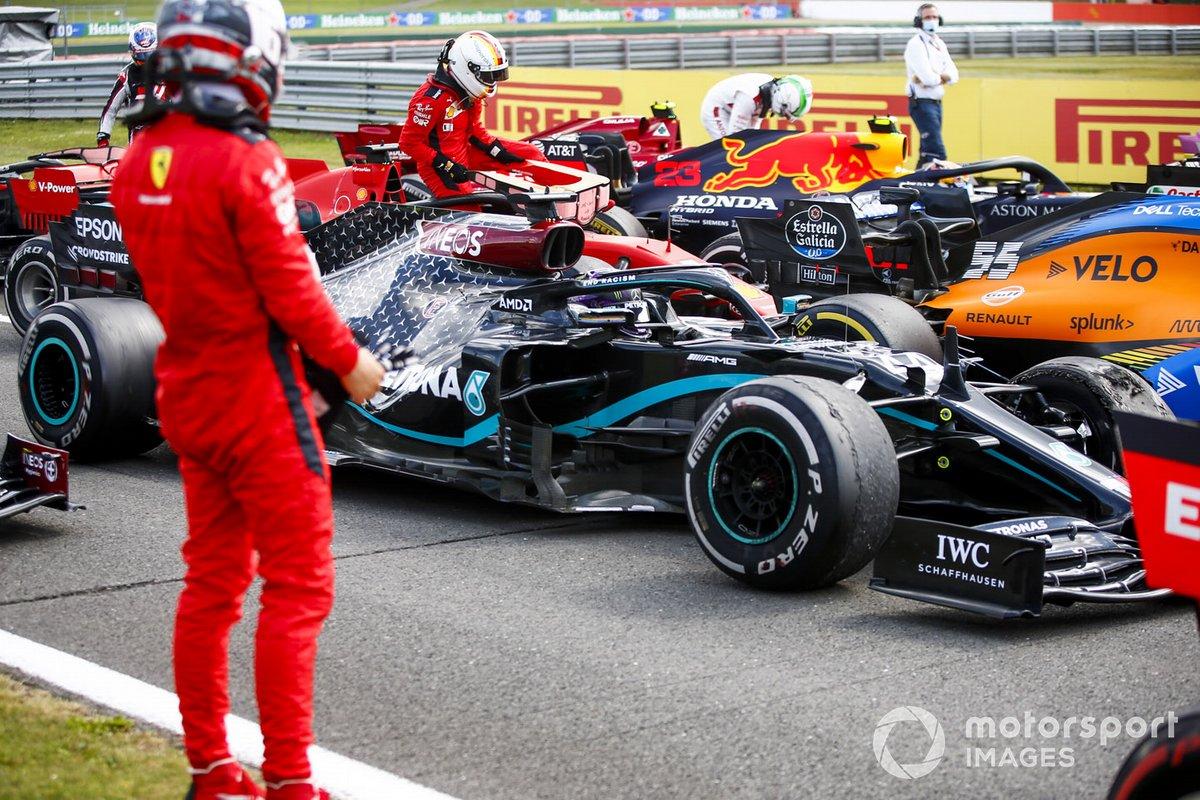 Charles Leclerc, Ferrari in Parc Ferme mira el neumático dañado del monoplaza de Lewis Hamilton, Mercedes F1 W11