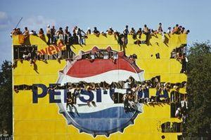 Les fans investissent un panneau publicitaire Pepsi pour voir la course