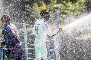 Pierre Gasly, AlphaTauri, 1st position, sprays champagne on the podium with Carlos Sainz Jr., McLaren, 2nd position