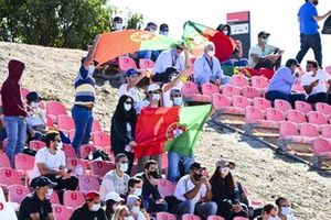 Fans wave Portuguese flags from a grandstand