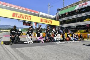 The driver stand and kneel in support of the End Racism campaign prior to the start