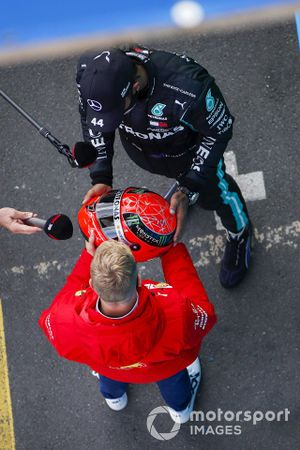Mick Schumacher, Alfa Romeo Racing, presents race winner Lewis Hamilton, Mercedes-AMG F1, with the Mercedes helmet of his father, Michael Schumacher, from 2012