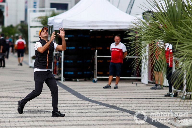 Carlos Sainz Jr., McLaren, catches a rugby ball