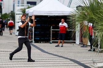 Carlos Sainz Jr., McLaren, catches a rugby ball