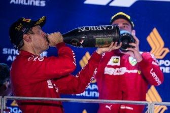 Sebastian Vettel, Ferrari, 1st position, and Charles Leclerc, Ferrari, 2nd position, drink Champagne on the podium