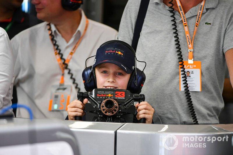 Un joven invitado en el garaje de Red Bull con el volante de Max Verstappen, Red Bull Racing