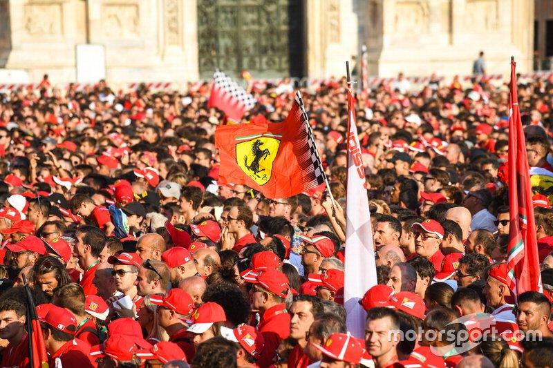 A Ferrari flag waves amidst the crowd