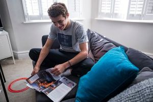 Lando Norris relaxes with a copy of Autosport Magazine