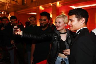 Lando Norris takes a selfie with a fan