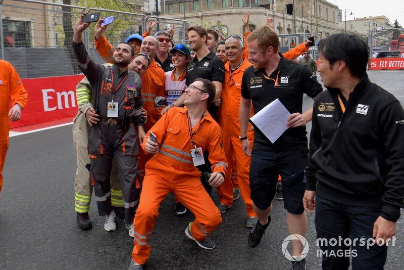 Romain Grosjean, Haas F1 toma un auto con los comisarios de pista mientras camina por la pista con sus ingenieros