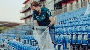 Sebastian Vettel, Aston Martin, ruimt plastic afval op na afloop van de Britse Grand Prix