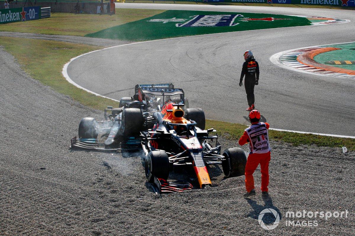 Max Verstappen, Red Bull Racing, se aleja mientras un oficial de pista asiste en el lugar de su accidente con Lewis Hamilton, Mercedes W12