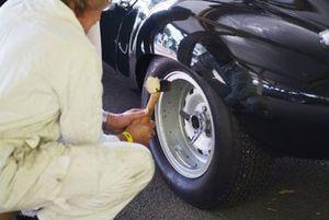 Un mécanicien travaille sur une roue de Jaguar E-Type