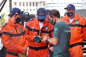 Sebastian Vettel, Aston Martin, signs a hat for a marshal