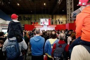 Una gran multitud se reúne para escuchar al presentador Stuart Codling entrevistando a Charles Leclerc, Ferrari en el escenario de Autosport