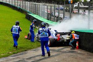 Marshals assist the smoking car of Daniil Kvyat, Toro Rosso STR14, with fire extinguishers