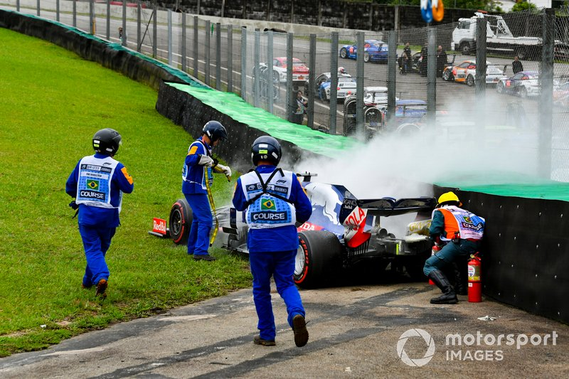 Marshals assist the smoking car of Daniil Kvyat, Toro Rosso STR14, with fire extinguishers