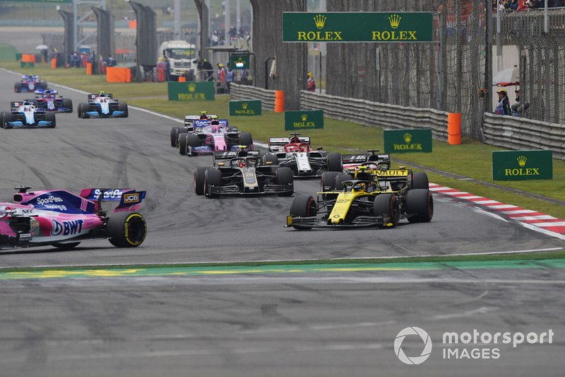 Sergio Perez, Racing Point RP19, leads Nico Hulkenberg, Renault F1 Team R.S. 19, Romain Grosjean, Haas F1 Team VF-19, Kevin Magnussen, Haas F1 Team VF-19, Kimi Raikkonen, Alfa Romeo Racing C38, Lance Stroll, Racing Point RP19, and the remainder of the field on the opening lap