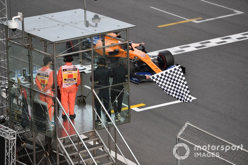 3 times world champion Alain Prost waves the chequered flag as Carlos Sainz Jr., McLaren MCL34 passes