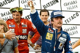 Keke Rosberg celebrates on the podium with John Watson