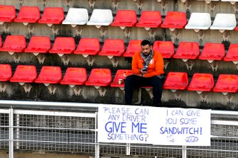 A fan sits behind a novelty banner, offering a trade of his lunch for a souvenir from a driver