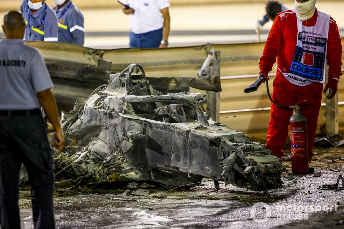 Marshals deal with the wreckage after a huge crash for Romain Grosjean, Haas VF-20, on the opening lap
