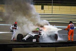 Kimi Raikkonen, Alfa Romeo Racing C39, assists a marshal in extinguishing a fire in his car