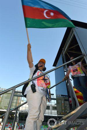 Oficiales de pista con la bandera de Azerbaiyán