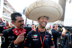 Daniel Ricciardo, Red Bull Racing, dons a sombrero, next to locals in traditional costume
