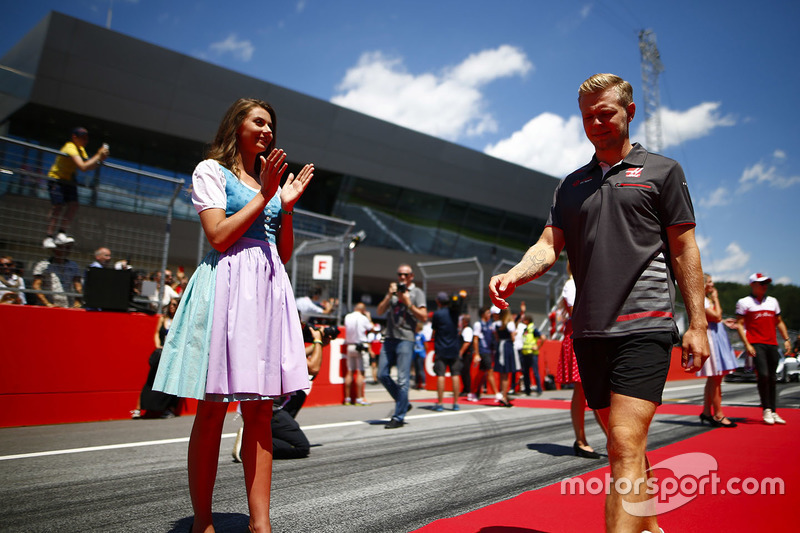Grid Girls in national costume flank the drivers parade as Kevin Magnussen, Haas F1 Team, passes