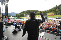 Fernando Alonso, McLaren, waves to fans from a stage