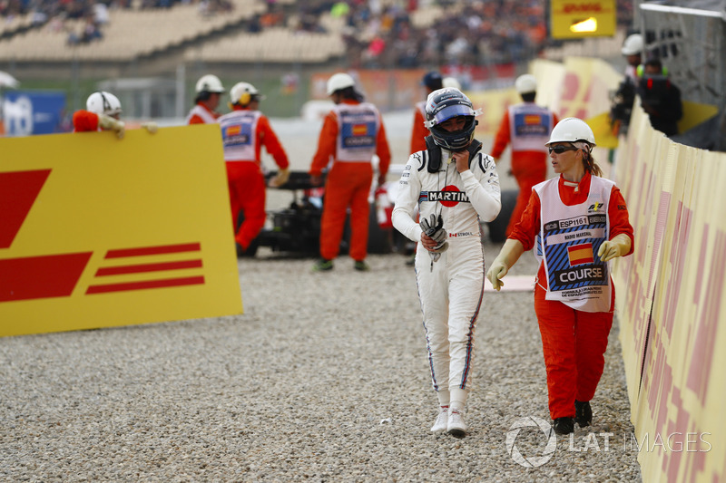 Lance Stroll, Williams Racing, is escorted by a marshal from his wrecked car