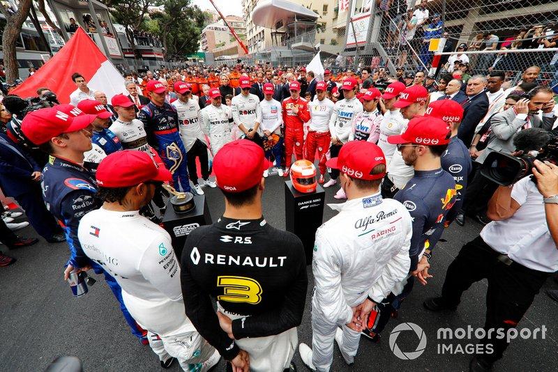 Pilotos en un minuto de silencio con gorra roja en homenaje a Niki Lauda