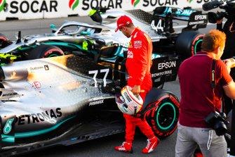 Sebastian Vettel, Ferrari, inspects the car of pole man Valtteri Bottas, Mercedes AMG W10, after Qualifying