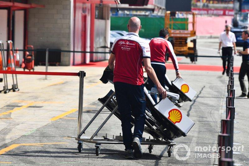 Un mécanicien pousse un aileron avant de l'Alfa Romeo Racing C38 dans la voie des stands