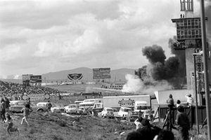 Il fumo che sale dai resti della BRM di Jackie Oliver e dalla Ferrari di Jacky Ickx che si è schiantato dopo che il mozzo anteriore di Oliver si è rotto nel giro di apertura