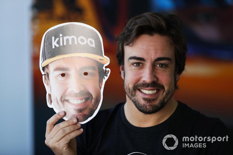 Fernando Alonso, McLaren, holds a face mask