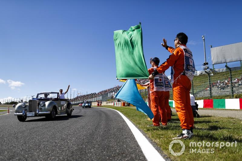 Des commissaires regardent Stoffel Vandoorne, McLaren, passer lors de la parade des pilotes