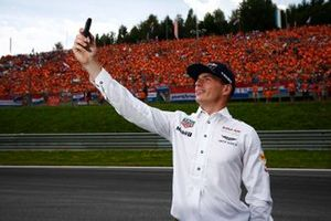 Max Verstappen, Red Bull, takes a photo with his Dutch fans in the background