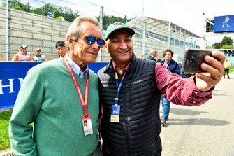 A fan takes a photo with Belgian racing legend Jacky Ickx