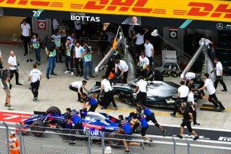 La Toro Rosso STR14 de Daniil Kvyat est poussée dans la voie des stands devant Valtteri Bottas, Mercedes AMG F1