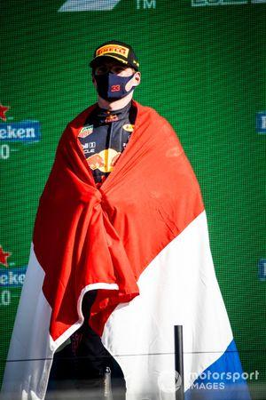 Max Verstappen, Red Bull Racing, 1e plaats, draagt een Nederlandse vlag als cape op het podium