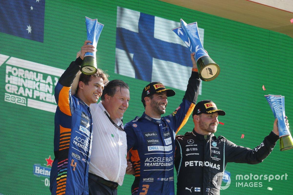 Lando Norris, McLaren, 2a posizione, Zak Brown, CEO, McLaren Racing, Daniel Ricciardo, McLaren, 1a posizione, e Valtteri Bottas, Mercedes, 3a posizione, sul podio