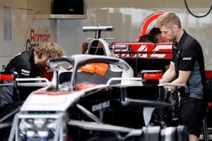 Haas mechanics work on their car in the garage