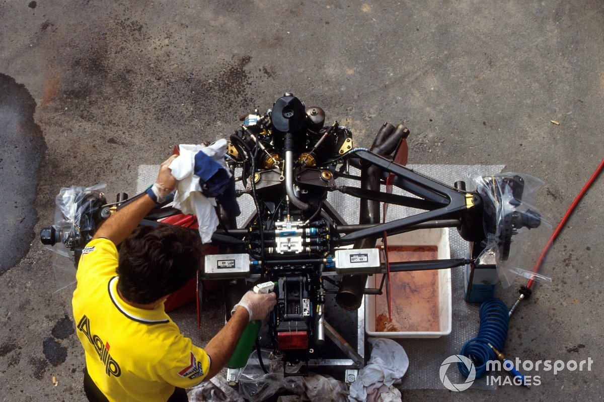 A Ferrari mechanic works on the back end of a stripped down Ferrari F92A