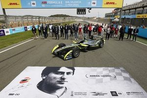 The drivers, Formula E personnel line up on the grid with the Gen1 car to pay tribute to Adrian Campos