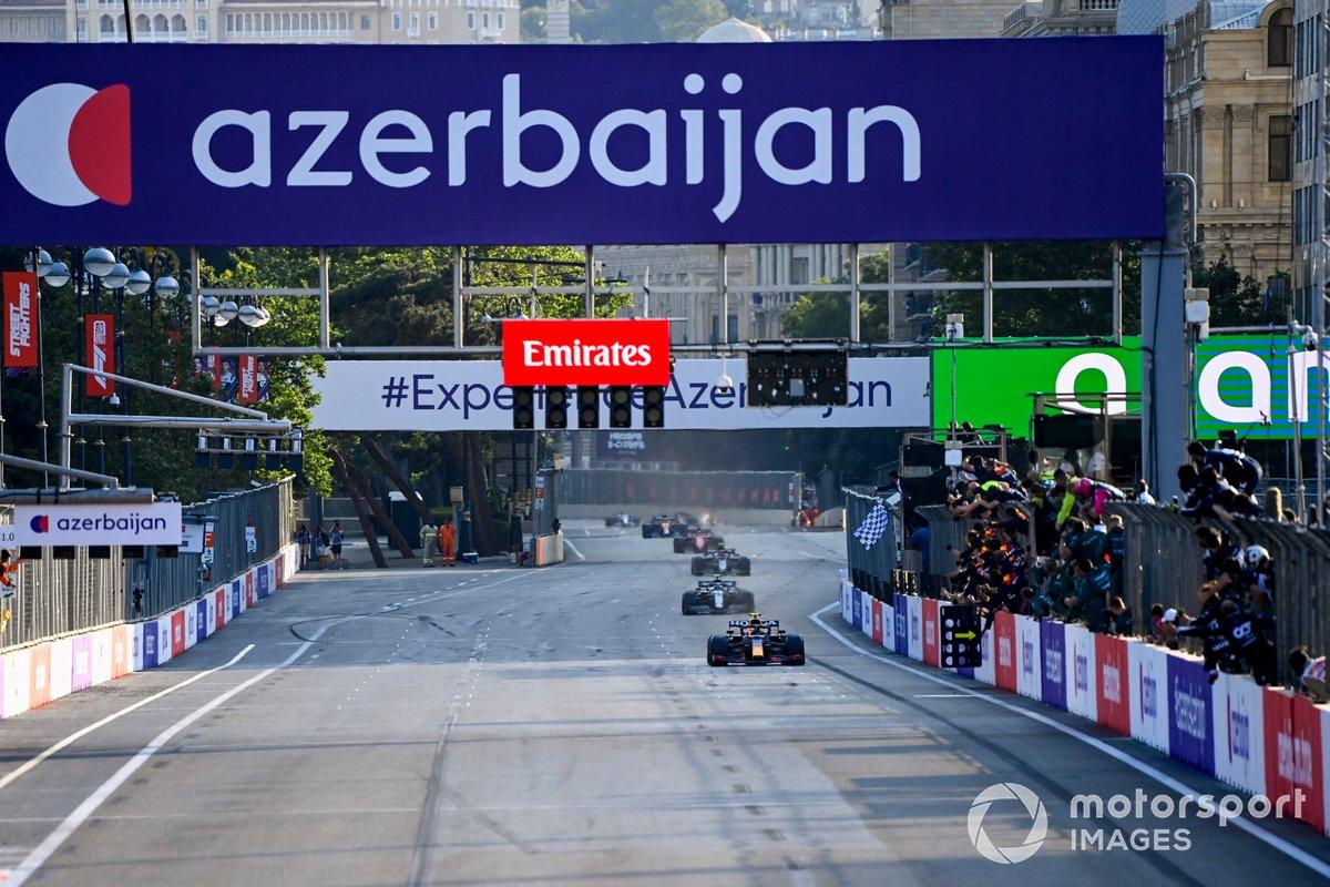 Sergio Pérez, Red Bull Racing RB16B, 1ª posición, toma la bandera a cuadros para alegría de su equipo en el muro de boxes