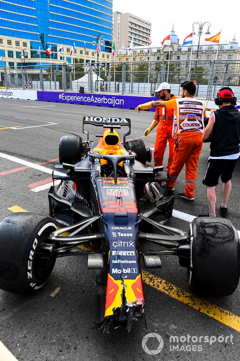 Oficiales de pista con el coche dañado de Max Verstappen, Red Bull Racing RB16B