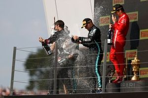 Lewis Hamilton, Mercedes, 1st position, Valtteri Bottas, Mercedes, 3rd position, Charles Leclerc, Ferrari, 2nd position, and the Mercedes trophy delegate celebrate with Champagne on the podium