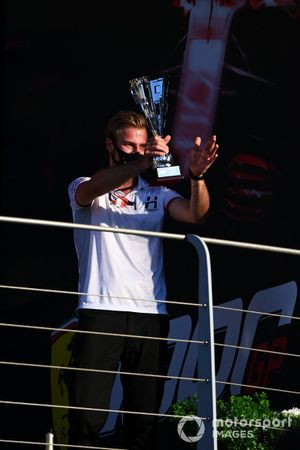The Hitech trophy delegate with the trophy on the podium